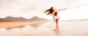 53171198 - young woman in sweater having fun enjoying beautiful sandy beach on the foggy weather on fuerteventura island in spain. general plan with a lot of space